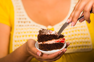 Woman holding small plate of chocolate cake with cream filling, grabbing bite using fork, showing to camera, pastry concept