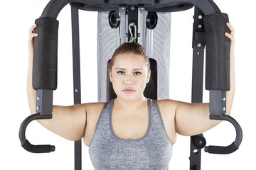 Woman exercising on a shoulder press machine