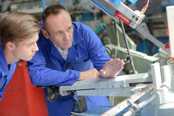 Man explaining working of machine to trainee