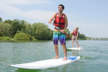 couple paddle boarding on lake
