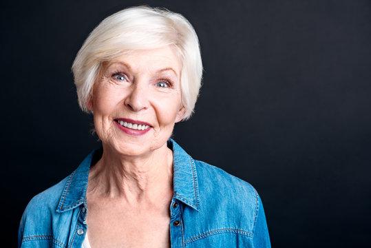 Cheerful elderly woman standign on black background