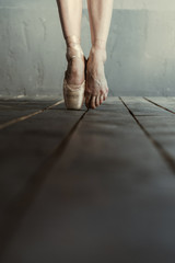 Ballet dancer standing on the tiptoes in the black room
