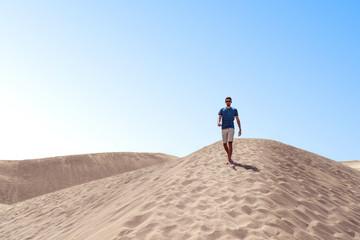 Man walking in desert dunes with sunglases