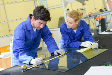 Young workers measuring pane of glass