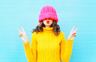 Fashion young woman blowing red lips makes air kiss wearing knit