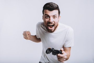 Young guy with beard holding joystick pretending he is playing games