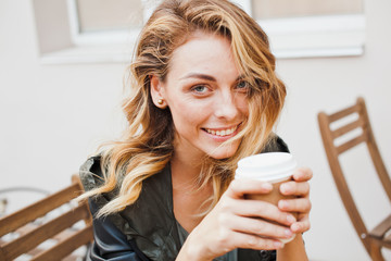 Young woman wearing casual outfit drinks coffee at cafe terrace