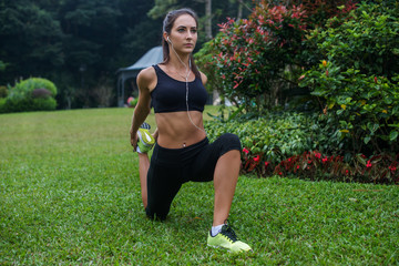 Fit girl doing kneeling quads stretch exercise in park. Young athletic woman working out and listening to music in her headphones outdoors.