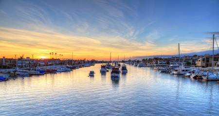 Balboa Island harbor at sunset with ships and sailboats visible from the bridge that leads into Balboa Island, Southern California, USA Wall mural