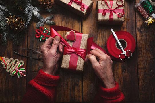 hands of senior woman making handmade New Year's or Christmas gi