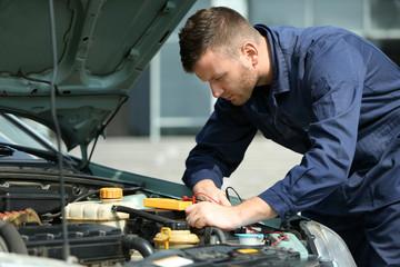 Mechanic with scan tool diagnosing car in open hood. Closeup