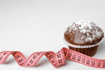 Dieting concept. Tasty chocolate cupcake and measuring tape on white background