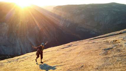 Female climber topping out of Snake Dike at sunset, Half Dome, Yosemite