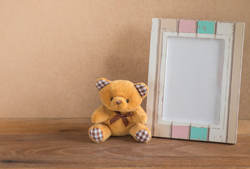 Teddy bear and photo frame on wooden background