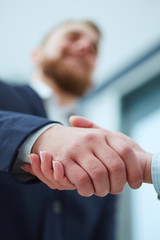 Male and female handshake in office.  Focus on hands.
