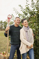 Happy couple standing with fruit picker in apple orchard