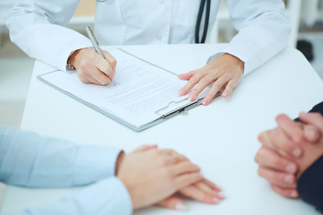 Closeup of patients hands and doctor taking notes. Ward round, patient visit check, medical calculation and statistics concept. Physician ready to examine patient