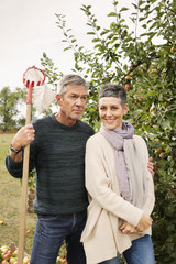 Portrait of happy woman standing with man in apple orchard