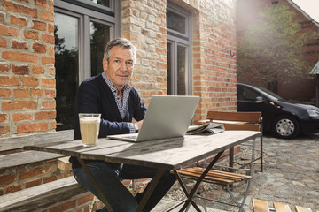 Portrait of mature man with laptop sitting in back yard