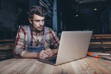 Carpenter using laptop while sitting in workshop