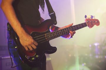 Bass guitar player, close-up photo