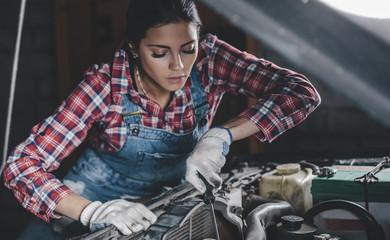 Female mechanic repairing car engine at workshop