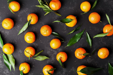 Tangerines or mandarins with green leaves on vintage black table from above in flat lay style.