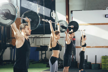 Side view of athletes lifting barbells at gym