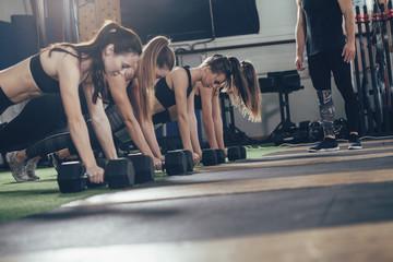 Determined athletes doing push-ups on dumbbells at gym