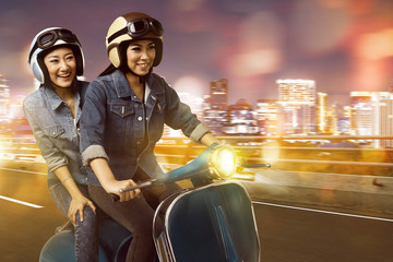 Happy two young asian woman having fun riding the scooter