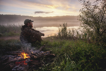 Side view of hunter sitting by bonfire on field at lakeshore during sunset