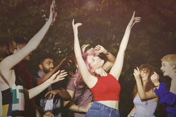 Excited woman dancing with friends at yard during party