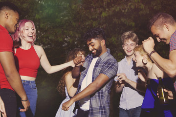 Cheerful multi-ethnic friends dancing at yard during party