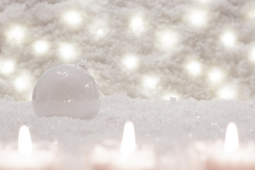 Glass white ball is in the snow. Christmas decoration, beautiful bokeh is in the background.