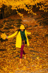 Happy girl in coat  with maple yellow leaves, autumn time