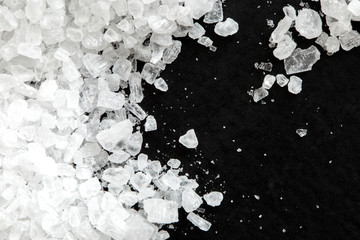 Closeup of coarse salt crystals on black from above. Wall mural