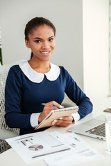 Vertical image of african business woman with notebook