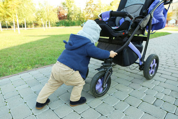 Cute little baby pushing violet stroller outdoors