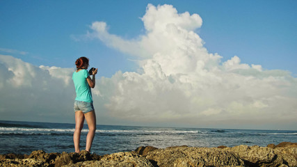Young woman with red hair in glasses photographs sea standing on the rocks , beach of Dominican Republic