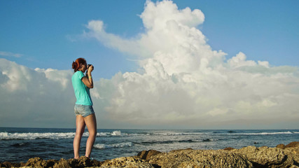 Young woman with red hair in glasses photographs sea standing on the rocks , beach of Dominican Republic, wide angle