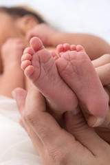 Pies de bebé recién nacido con las manos de su madre 1.