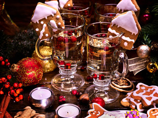 Four glasses of hot wine for whole family standing on wooden table. Christmas drinks decorated with Christmas cookies. Candles and Christmas balls in still life.