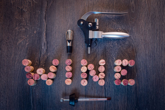 Wine word out of corks with wine accessories on wooden background
