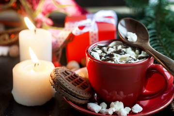 cup of cocoa with marshmallows and Christmas gifts in the backgr