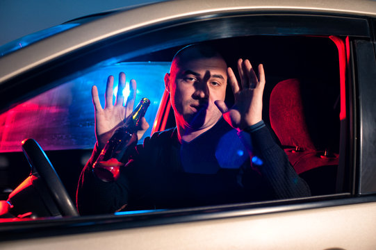 Man with beer bottle in car surrendering to police