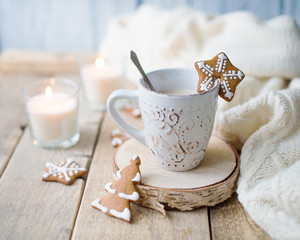 Cup of hot chocolate with gingerbread and candle.