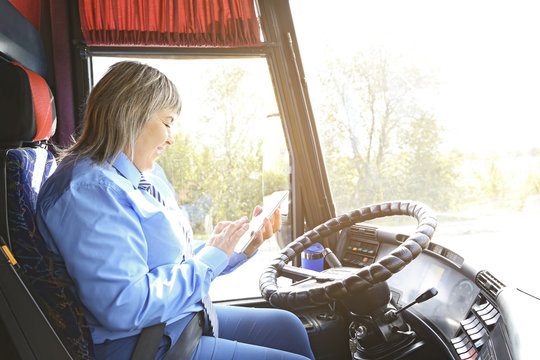 Female driver using tablet in bus