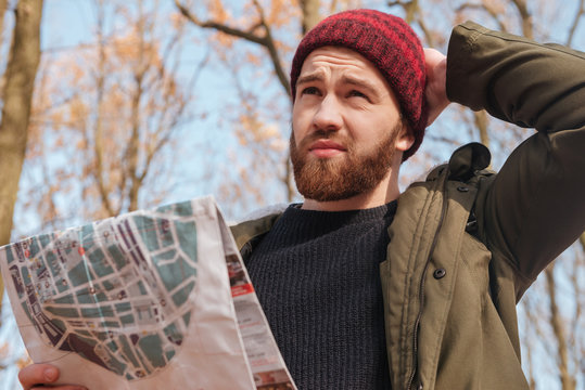 Confused bearded man wearing hat holding map in hands