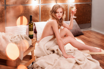 Naked woman wrapped in a blanket with bottle and glass of white wine. Beautiful blonde girl enjoying alcohol. Cozy evening, winter holidays