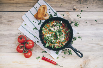 Delicious fresh morning Shakshuka on the wooden rustic table with some tomatoes on the side